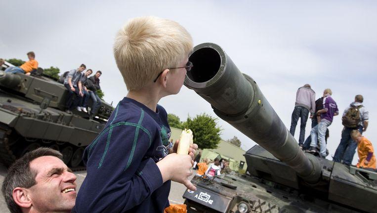 Open dag in de Johannes Postkazerne in Havelte, 2010: een vader tilt zijn zoon op om hem in de loop van een Leopard-tank te laten kijken. Beeld ANP