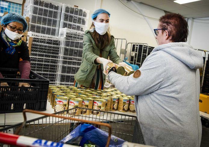 Vrijwilligers van de Tilburgse Voedselbank delen voedselpakketten uit.