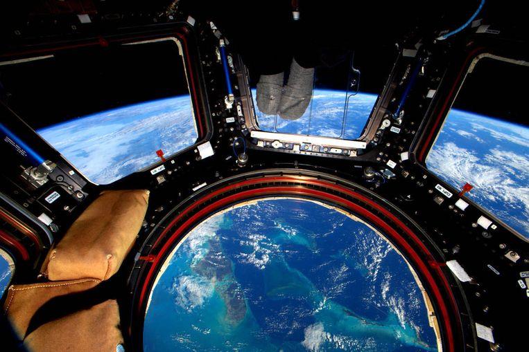Het ISS, de voeten van Scott Kelly en een uitzicht over de Bahama's.