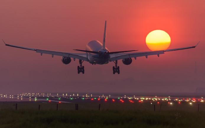 Een vliegtuig landt op Schiphol tijdens zonsopkomst.
