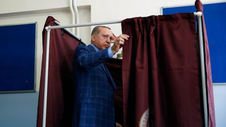 President Erdogan betreedt het stemhokje om zijn stem uit te brengen voor het referendum. Istanbul, 16 april. Beeld ap