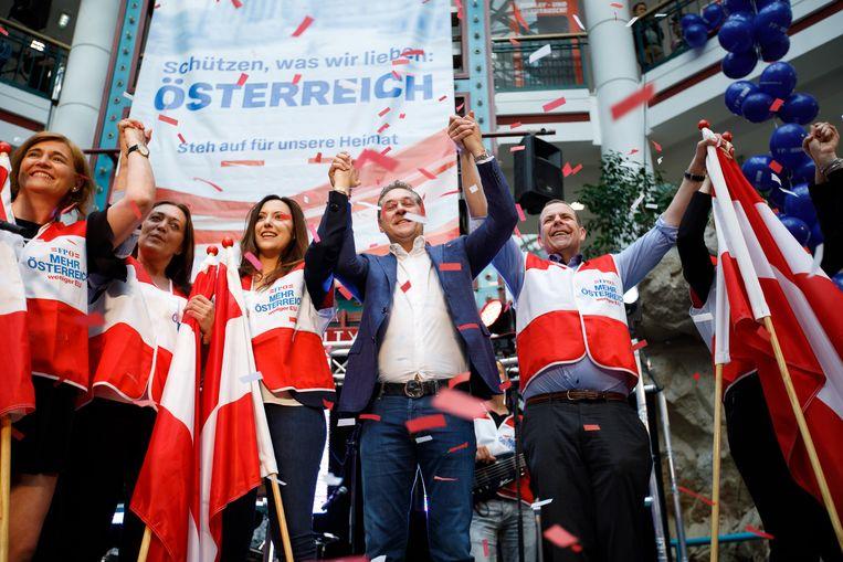 'Meer Oostenrijk, minder EU' staat er op de hesjes. FPÖ-leider Heinz Christian Strache (in het midden) trapt de campagne voor de verkiezingen voor het Europees Parlement af. Op de vlag erachter de leus: 'Sta op voor onze Heimat'.  Beeld EPA