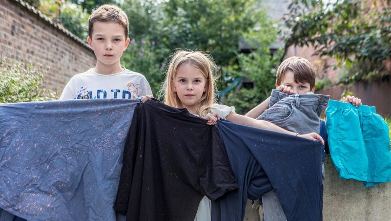Kinderen Pepijn, Janneke en Gabriel tonen hun kapotte kleding.
