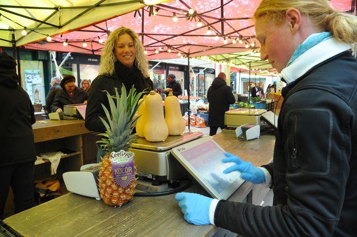 Verkoopster Anna van de Fruit Shop met blauwe handschoentjes aan het werk met de kassa op de markt in Vlissingen.