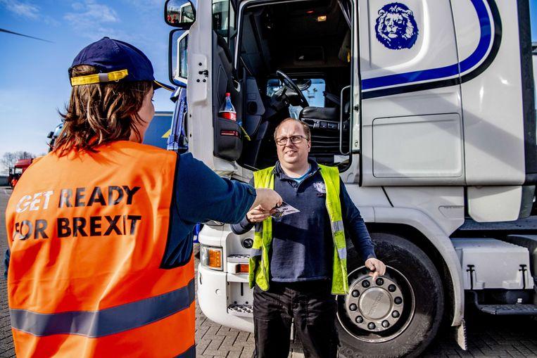 Een vrouw deelt in de haven van Rotterdam flyers uit waarin truckchauffeurs worden ingelicht over de formaliteiten na de brexit.