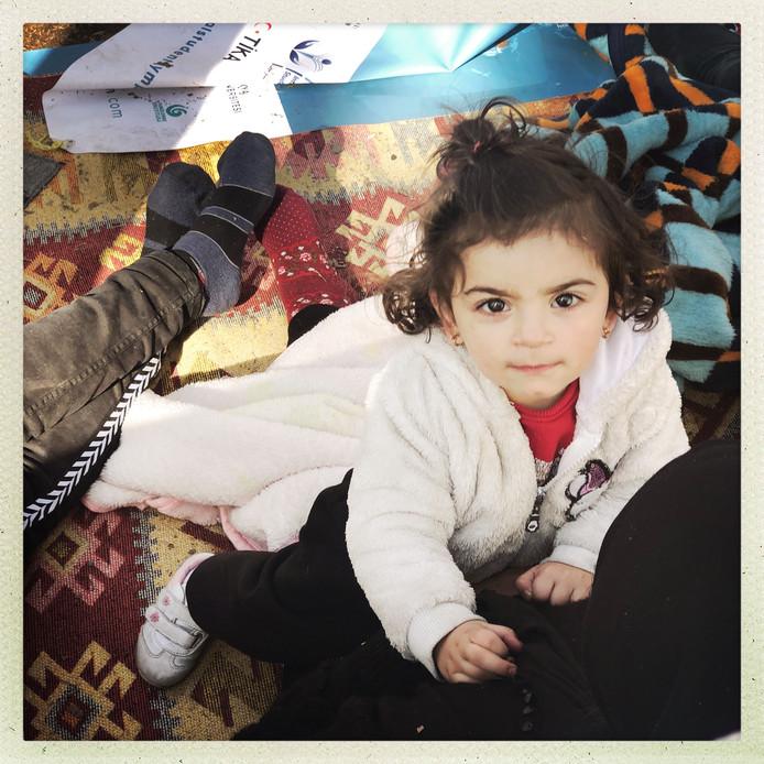 Ook dit meisje zit vast op de grens tussen Turkije en Griekenland, maar zij is er wel met haar ouders.