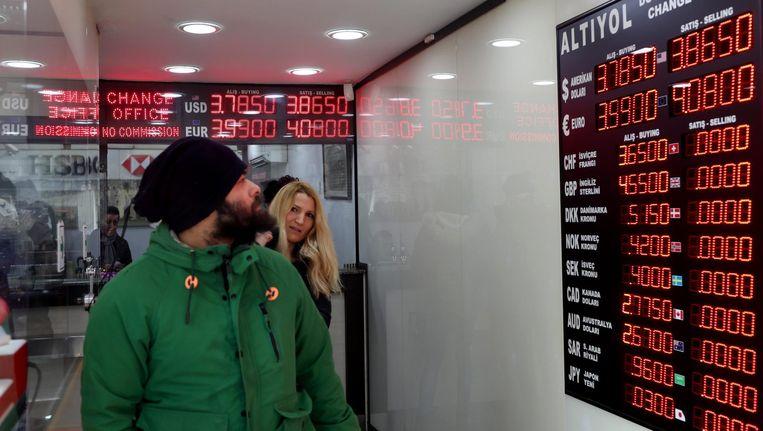 Mensen bekijken op 11 januari de wisselkoers in een wisselkantoor in Istanbul, Turkije. Beeld epa