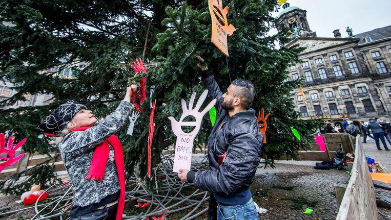 Kunstenaar Godelieve Smulders hangt met de passerende Furkan Yildirim een protesthand in de boom op de Dam Beeld Jean-Pierre Jans