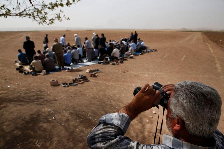 Inwoners van Mursitpinar, een buitenwijk van Suruc, bekijken van een afstandje de gevechten in Kobani. Beeld AP