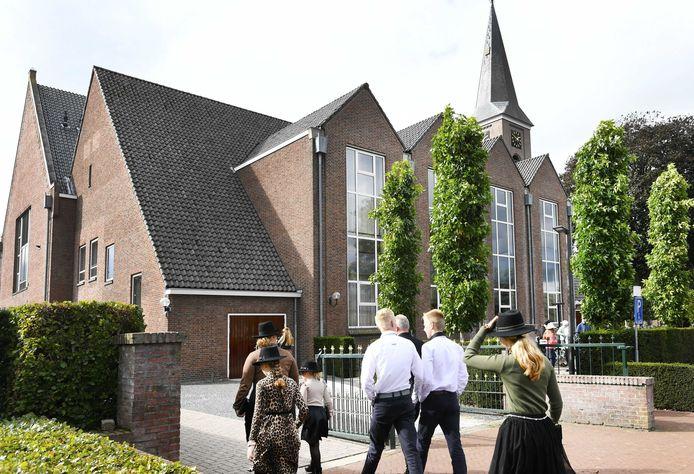 Kerkgangers komen aan bij de Hersteld Hervormde Kerk in het diepgelovige dorp Staphorst.