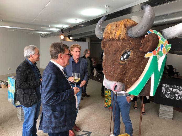 Samen met Dolf de Mooy (links) van het Kunstation Uden bekijken burgemeester Hellegers en Bakermans het kunstwerk met deze koppen als middelpunt.