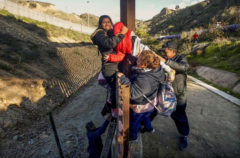 Hondurese migranten klimmen over het hek bij de Amerikaans-Mexicaanse grens in de buurt van Tijuana op 6 januari.
