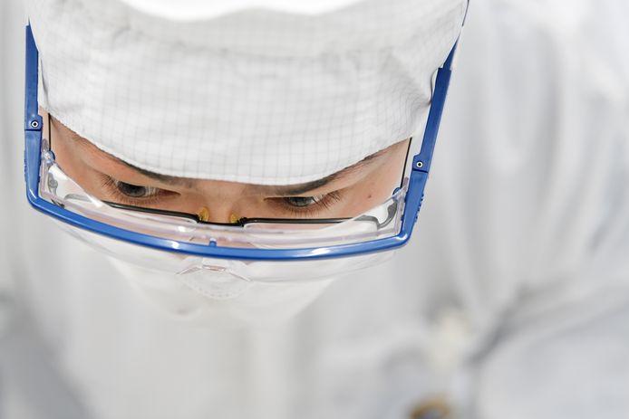 Een werknemer van ASML concentreert zich in de cleanroom bij de productie van chipmachines.