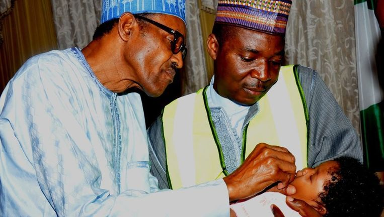 De Nigeriaanse president Muhammadu Buhari (links) vaccineert zijn kleindochter tegen polio Beeld epa