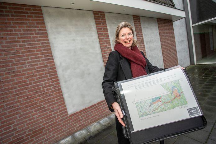 Colette Beckers met het eerste ontwerp voor het tegeltableau voor de indertijd nog kale hoek, waar inmiddels de Syrische supermarkt zit.