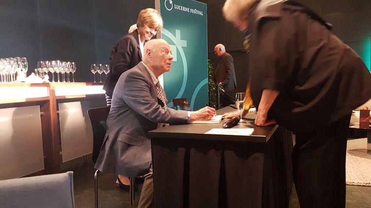 Bernard Haitink signeert in Luzern, aan de vooravond van zijn laatste concert.  Achter hem zijn vrouw Patricia. Beeld Guido van Oorschot