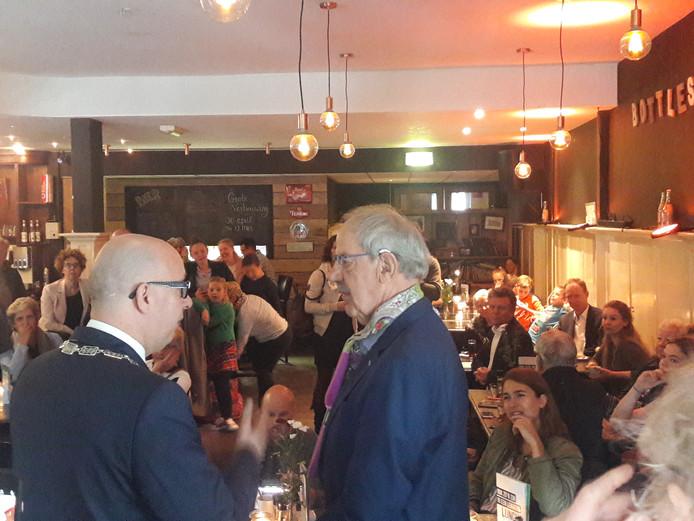 Burgemeester Jack Mikkers (links) vertelt Wil van den Elzen (80) dat hij later op de dag een koninklijke onderscheiding in ontvangst mag nemen.