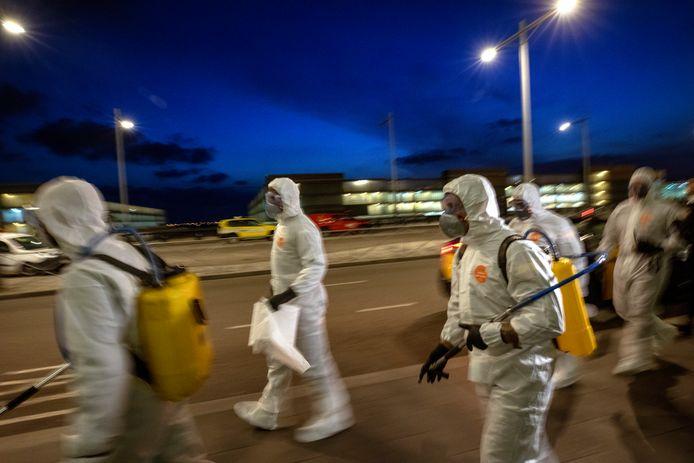 Soldaten maken zich op om de terminal van de luchthaven in Barcelona te ontsmetten.