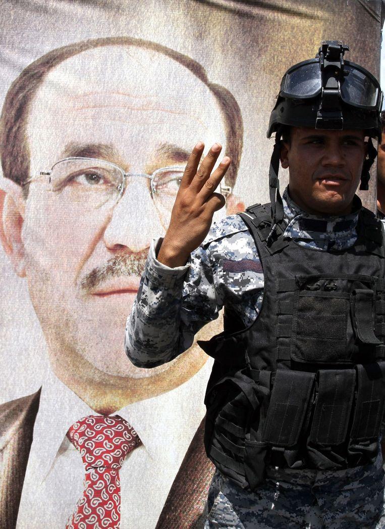 Een Iraakse politieagent toont drie vingers voor een poster van zittend premier Nouri al-Maliki, waarmee hij refereert aan een derde termijn voor Al-Maliki. Beeld epa