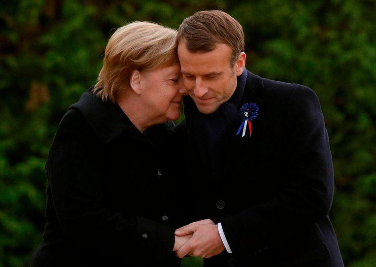 De Duitse bondskanselier Angela Merkel en de Franse president Emmanuel Macron omhelzen elkaar en houden elkaars handen vast nadat ze een tegel onthullen als onderdeel van de herdenking van de wapenstilstand honderd jaar geleden in Compiègne.