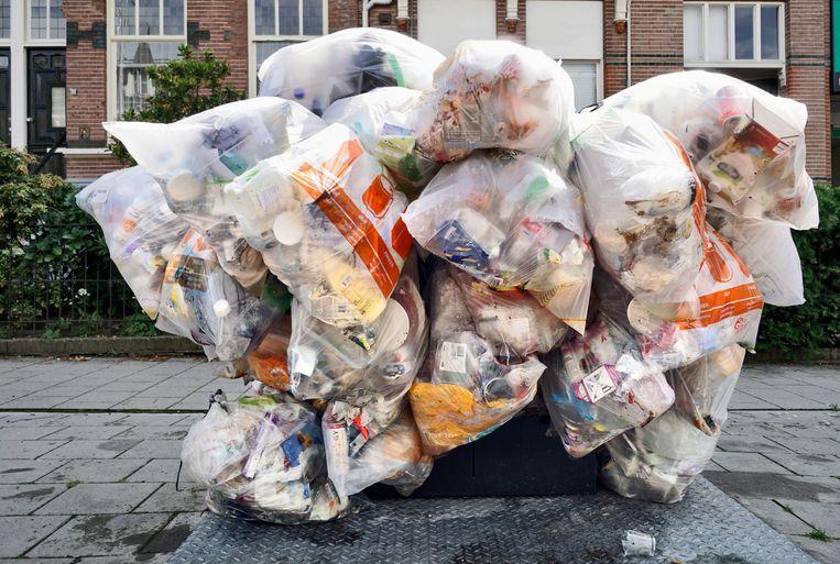In een straat met veel studentenhuizen in Nijmegen hangen zakken gevuld met plastic afval klaar om door de reinigingsdienst opgehaald te worden.  Beeld Flip Franssen / HH