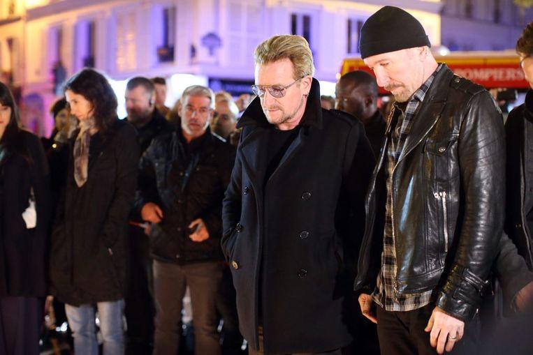 Leden van U2, onder wie Bono, bezoeken de bloemenzee bij concertzaal Bataclan. Beeld ANP