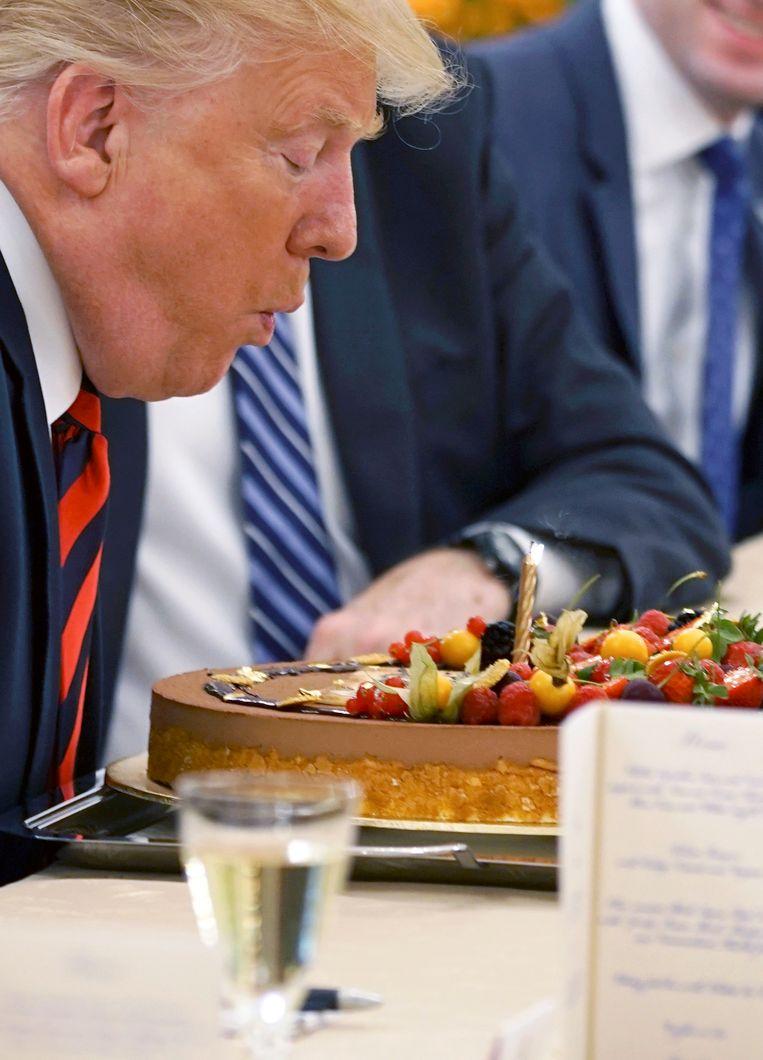 Donald Trump blaast tijdens een werklunch met de Singapores premier kaarsjes uit op een taart die hij gekregen heeft ter ere van zijn 72e verjaardag, die donderdag plaatsvindt.