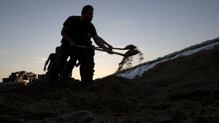 Nederlandse militairen verhogen een stuk dijk langs rivier de Elbe. Beeld anp