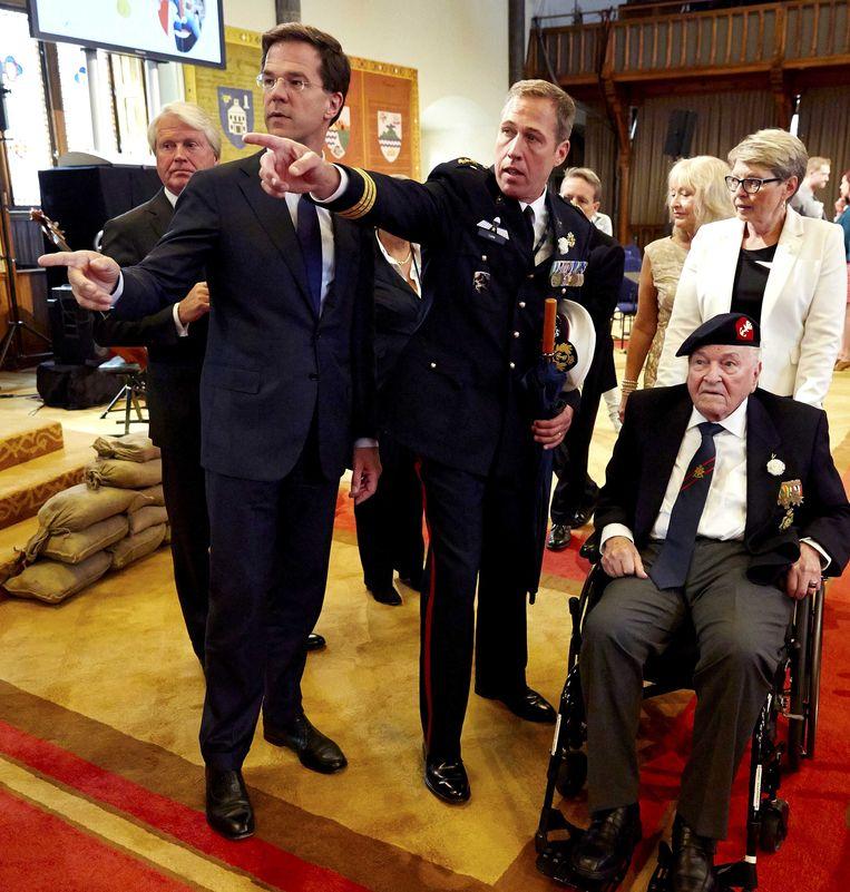 Minister-president Mark Rutte begeleidt veteraan Willem 'Bil' Ramakers als zij de Ridderzaal betreden voor de openingsceremonie van Veteranendag. Beeld ANP