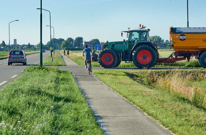 De plek waar de Langendonkweg aansluit op de John F. Kennedybaan in Oss. Het fietspad wordt hier straks vier meter breed en komt rechts van dit smalle pad te liggen.