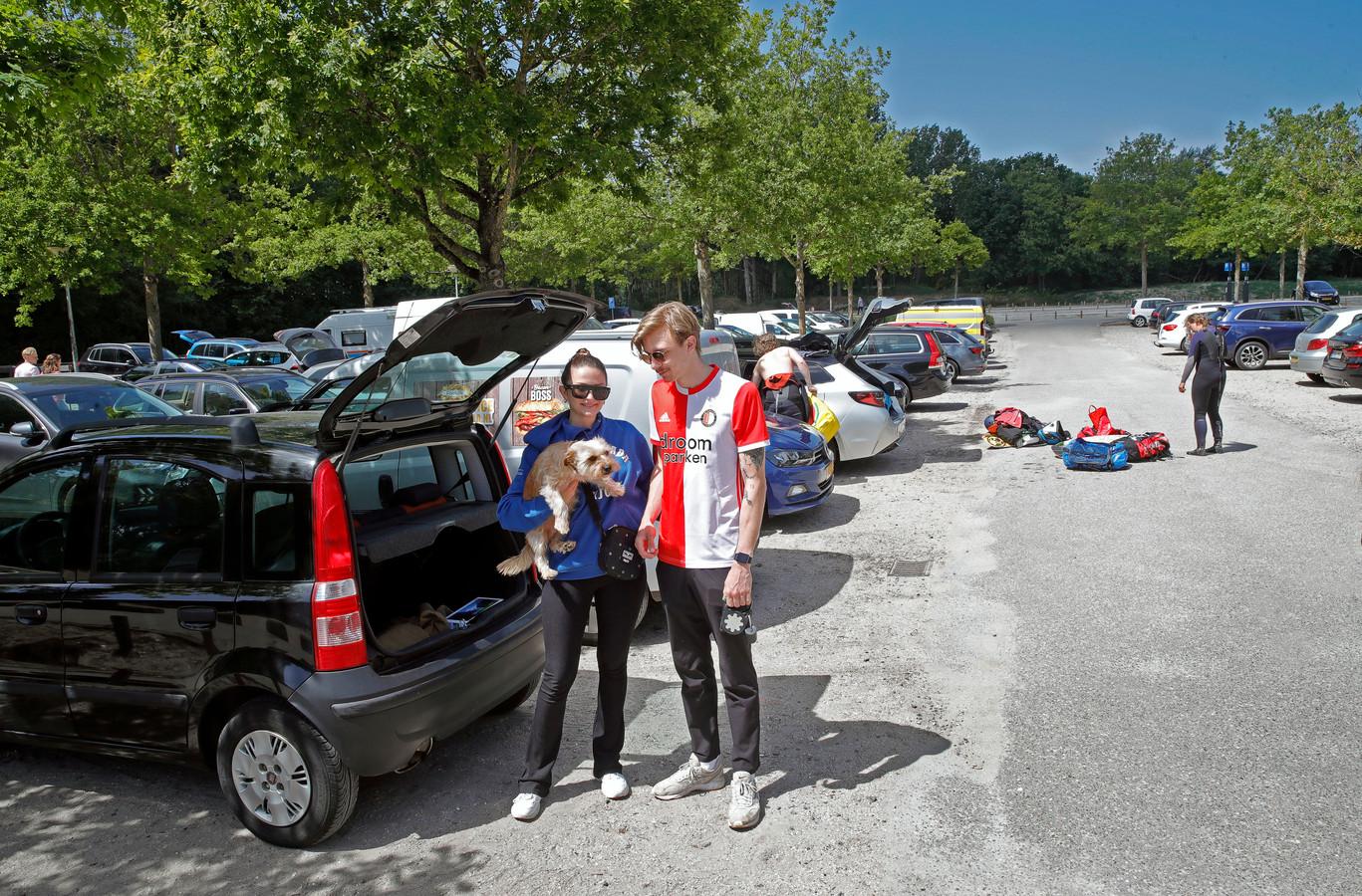 Maddie en Tom met hond Elton op de parkeerplaats aan de Eerste Slag, daarachter verkleden kitesurfers zich.