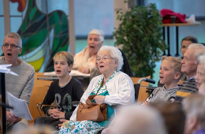 Kinderen zingen samen met ouderen.