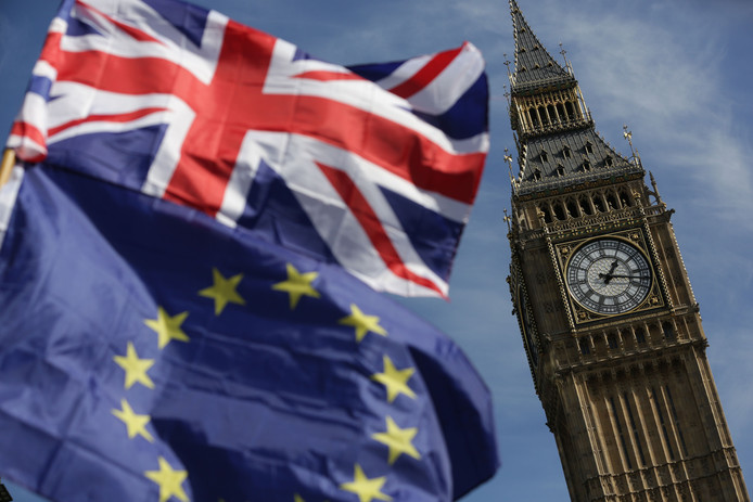 De Big Ben in Londen, met op de voorgrond de Britse en Europese vlaggen.