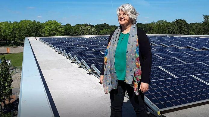 Wethouder Klaar Koenraad op een dak met zonnepanelen, in dit geval het dak van het JTC.