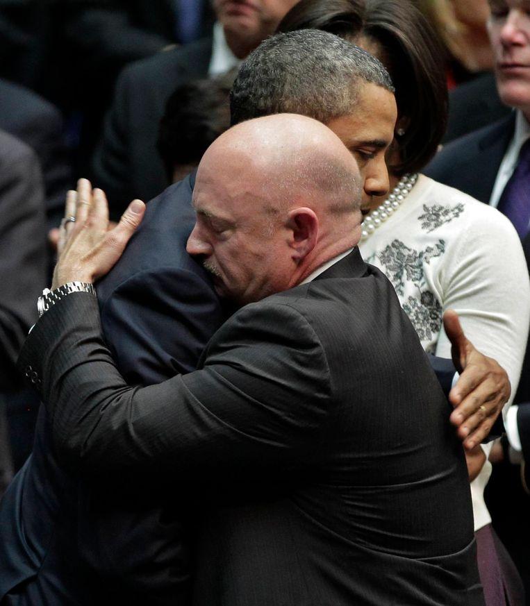 Voormalig Amerikaans president Barack Obama omhelst Mark Scott, tweelingsbroer van Scott en man van Senator Gabrielle Giffords die neergeschoten werd.