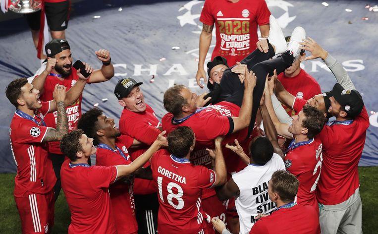 Hans-Dieter Flick, coach van Bayern München, wordt door zijn team opgetild na het winnen van de Champions League. Beeld EPA