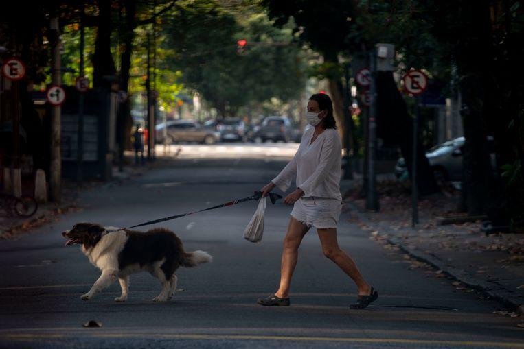 Een vrouw met een masker laat in de Braziliaanse stad Rio de Janeiro haar hond uit. Beeld AFP
