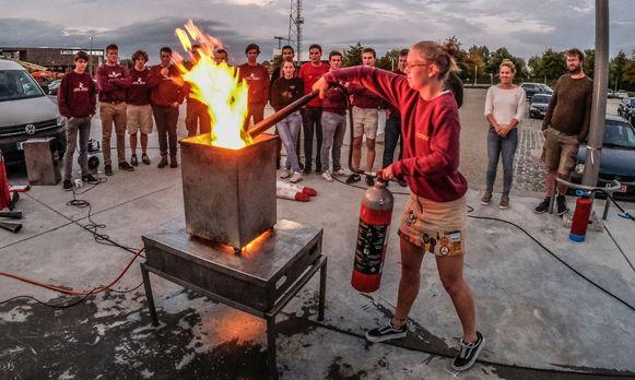Jongeren leren hoe je een brand in een vuilnisbak aanpakt.