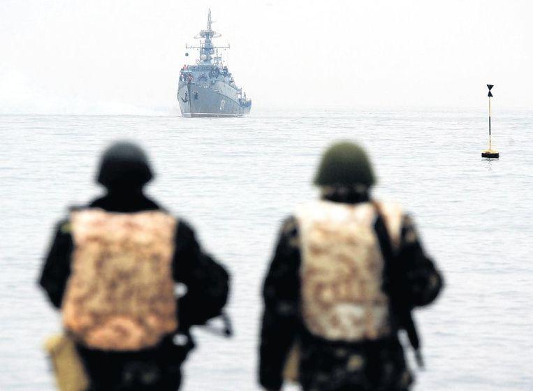 Oekraïense militairen kijken naar een Russisch marinevaartuig dat voor de haven van Sebastopol in de Zwarte Zee ligt. Beeld afp