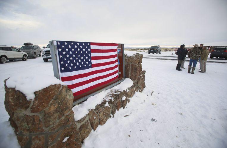 De Amerikaanse vlag hangt over het bord bij de ingang van het complex. Beeld REUTERS