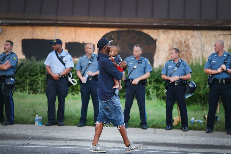 Een man loopt met zijn kind in zijn armen langs politieagenten. Beeld getty
