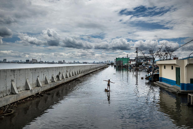 NOORD-JAKARTA,INDONESIË, 2018. Deze muur moet bescherming bieden, maar doet dat onvoldoende. Noord-Jakarta verzakt 25 centimeter per jaar. Gebeurt er niets, dan staat dit stadsdeel in 2050 onder water. De stad wil een nieuwe muur bouwen, maar er bestaan ook plannen om heel Jakarta te verhuizen.