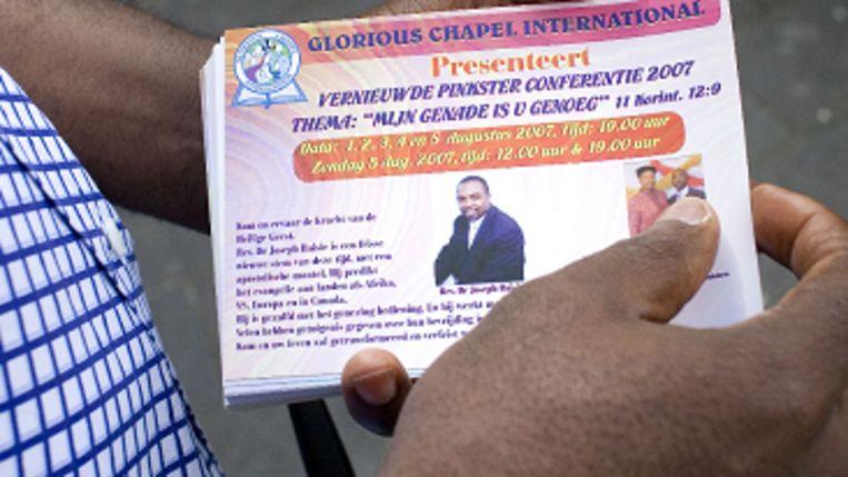 Pastor Olada Asubiaro van de 'Glorious Chapel International' in Rotterdam deelt flyers uit. (Joel van Houdt) Beeld