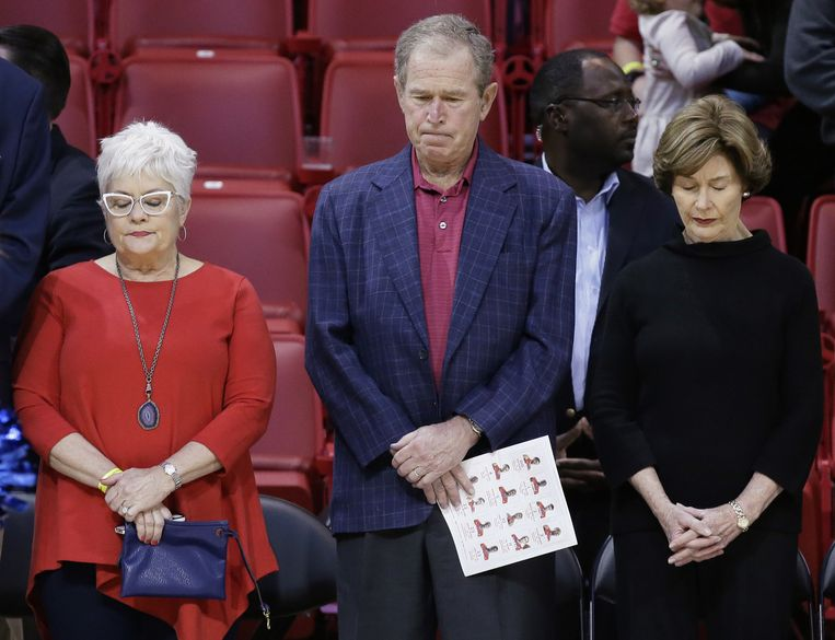 Voormalig Amerikaans president George W. Bush met zijn vrouw (L) herdenkt de slachtoffers van de aanslagen in Parijs voor aanvang van een basketbalwedstrijd. Beeld ap
