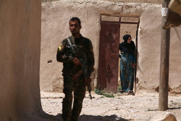 Een strijder van de SDF houdt de wacht in een buitenwijk van Manbij. Beeld reuters