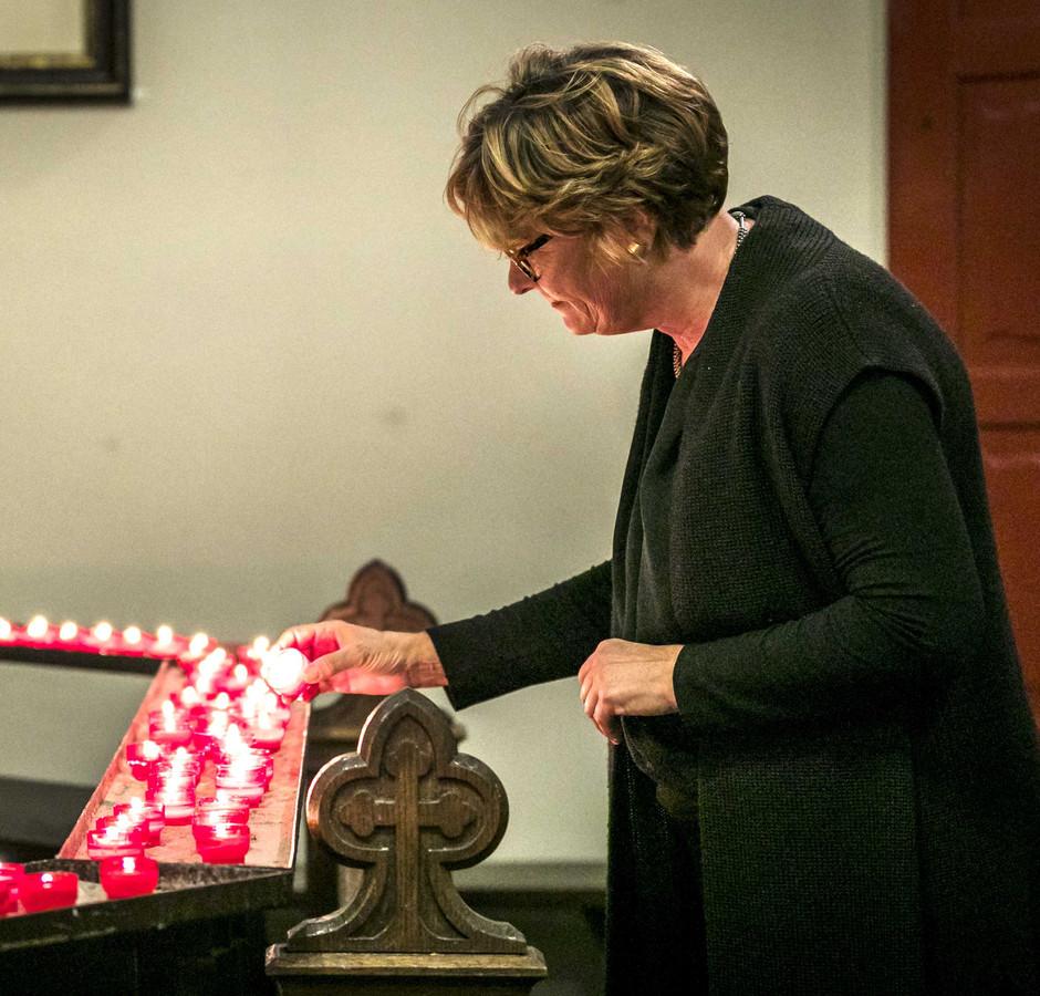 Burgemeester Wobine Buijs steekt een kaarsje aan ter nagedachtenis aan de vier omgekomen slachtoffers van het spoorwegongeval.