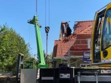 Loodzware machine kantelt tegen dak van woning, met ravage tot gevolg