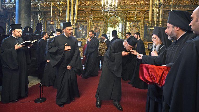 Orthodoxe geestelijken kussen tijdens een dienst in de St. George-kathedraal in Istanbul de hand van patriarch Bartholomeus. Beeld Guus Dubbelman / de Volkskrant