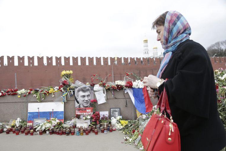 Een vrouw loopt langs de bloemenzee (donderdag 12 maart) op de plek waar Boris Nemtsov is doodgeschoten. Beeld epa