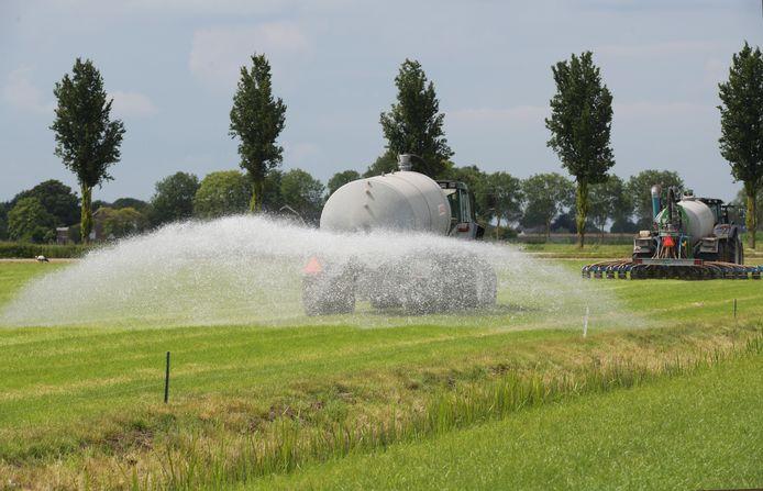Peter van Beest besproeit het weiland achter de mestinjecteur aan in Lienden